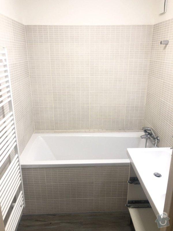 Původní koupelna s vanou a béžovými obklady.