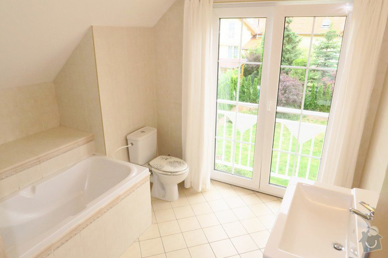 Původní koupelna s vanou a světlými obklady.